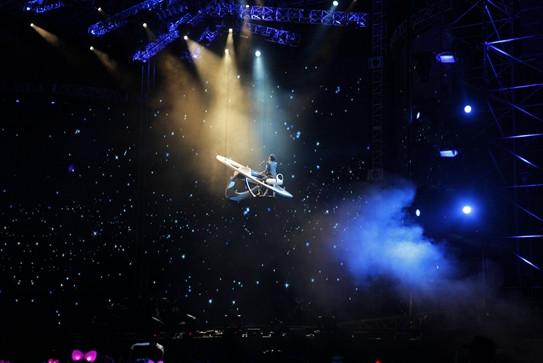 """此次王力宏深圳演唱会,王力宏再度化身为""""MUSIC-MAN"""",整场演唱会除了充满未来感的漫画元素,更是将极富视觉冲击力的巨型道具搬上舞台。王力宏深圳演唱会制作团队不惜重金打造气势磅礴的开场视频,试图在现场呈现出烟硝弥漫的战争场景。随后王力宏以一身红色荧光盔甲战袍驾驶一辆坦克驶入舞台中央,一场属于王力宏深圳演唱会的音乐战役正式拉开序幕。而现场立刻也随着这个""""重型武器""""的登场进入了演唱会的第一个高潮。而这个""""大家伙""""也是演唱会制作团队按照实体坦克一比一的比例制作的道具。外形绝对可以以假乱真。这"""
